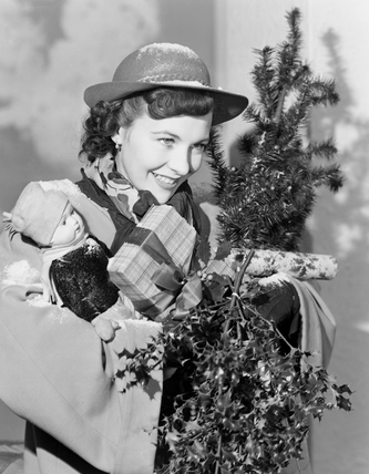 Woman carrying Christmas presents, c 1949.