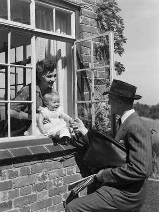 Man saying goodbye to a woman and baby, 1951.