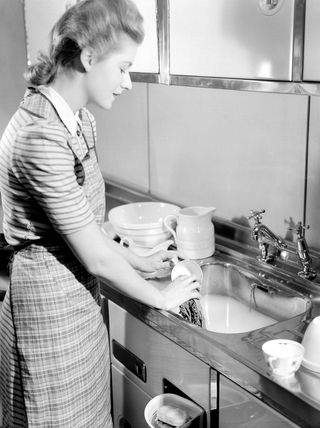 Woman doing the washing up, 1950.
