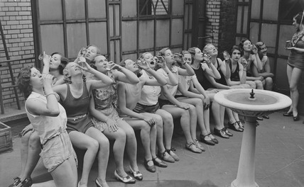 Dancers drinking from a water fountain, c 1930s.