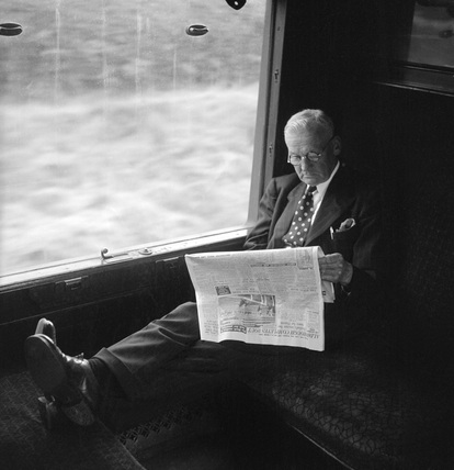 Man with his feet up reading a newspaper during a train journey, 1950.