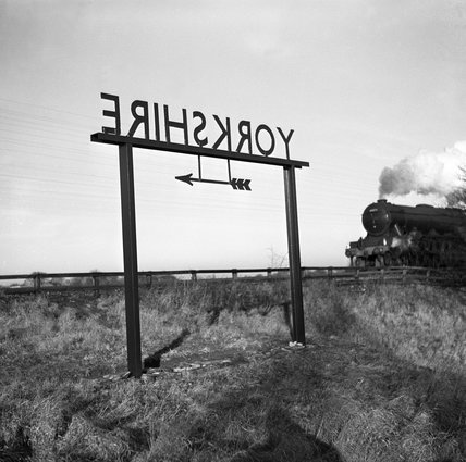 Train approaching a 'Yorkshire' sign on the boundary with County Durham, 1951.