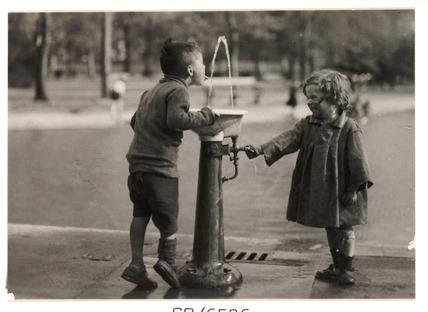 Two children at a drinking fountain, c 1910