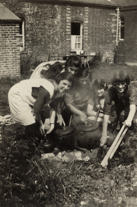 Group of girls with cooking pots, c 1920s.