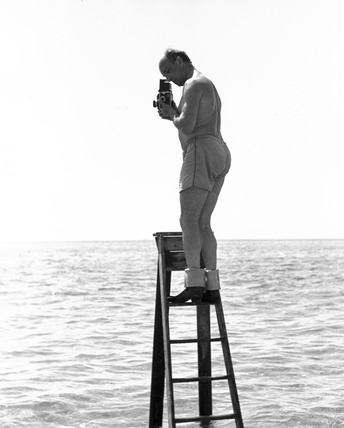 Zoltan Glass taking a photograph standing on a ladder in the sea, c 1964.