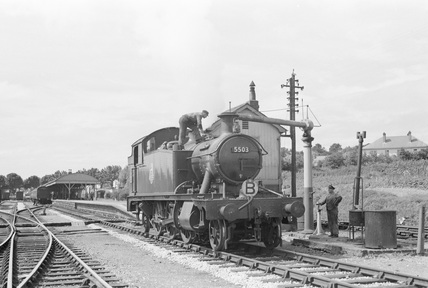 Locomotive no. 5503 at Barnstaple taking water. Driver Vinnicombe at the stop cock. 28 July 1951