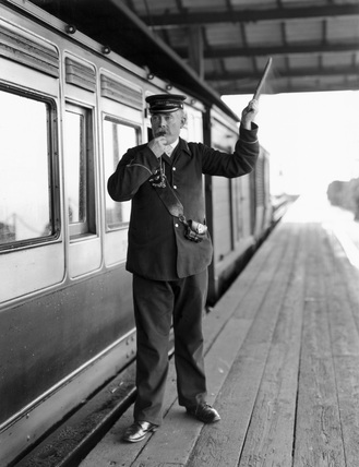 A guard giving signal for departure, 1905.