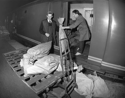 Loading sacks of mail into the sorting van of the Travelling Post Office, c.1987.