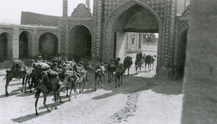 Camels ladened with saddlebags passing through a North African courtyard, c 1910s.