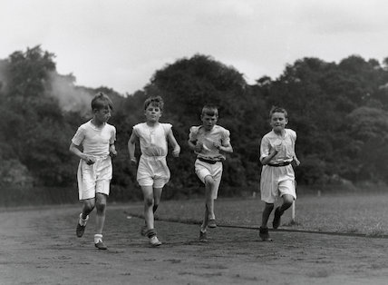 Four boys in sports kit running around a bend on a racetrack, c 1920s.