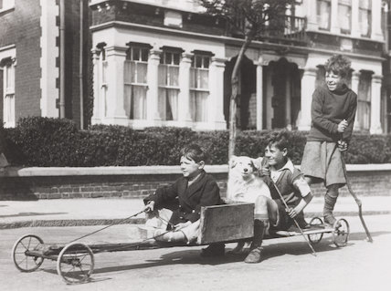 Boys riding down a road in a home-made cart, c 1930s.