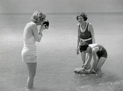 Woman in a bathing costume filming friends in the sea, c 1930s.