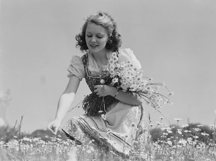 Young woman with an armful of daisies, c 1930s.