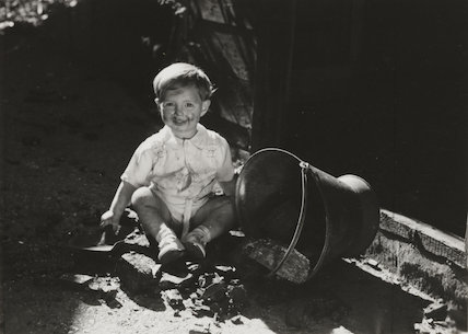 Dirty- faced young boy with a coal scuttle, c.1930.