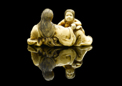 Ivory netsuke showing a mother breast-feeding a child, Japan, 18th-19th century.