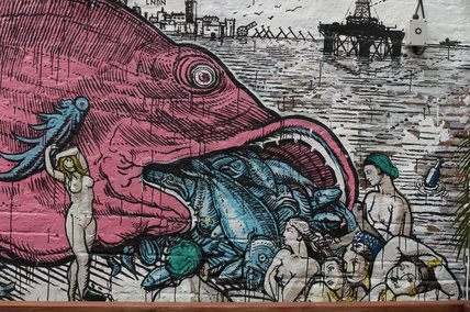 Graffiti of big fish eat small fish by Ozmo in East London