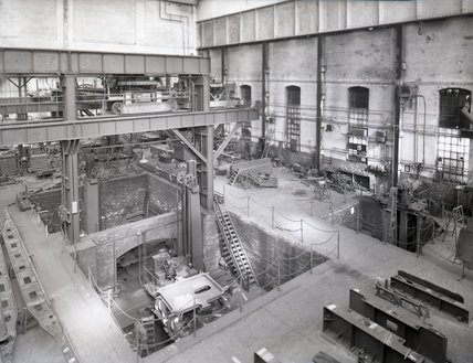 Works photographic negative of interior view of the boiler shop showing shell drills and a hydraulic riveter, 1959.