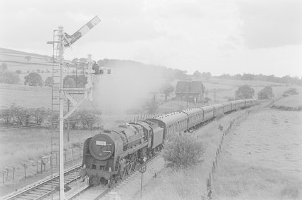 A steam locomotive pulling a passenger train, approaching signals. Locomotive number: 1S80,A1969.70/Box 5/Neg 1236/30