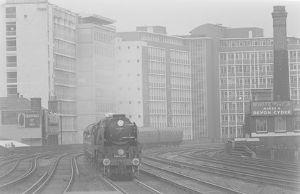 A steam locomotive pulling a passenger train, entering a station,A1969.70/Box 5/Neg 1238/5