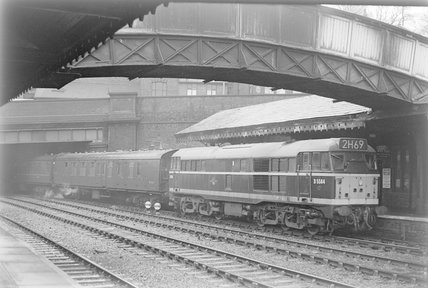 A diesel locomotive with a passenger train in a station,A1969.70/Box 5/Neg 1249/17