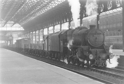 A steam locomotive with a goods train at a platform,A1969.70/Box 5/Neg 1262/6