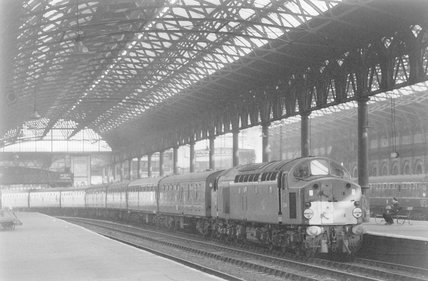 A diesel locomotive pulling a passenger train, arriving at a station,A1969.70/Box 5/Neg 1262/7