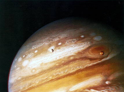 The planet Jupiter, showing two of its moons and the Great Red Spot, 1979.