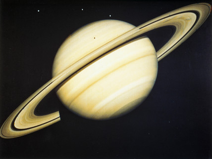 The planet Saturn and three of its moons, 1981.