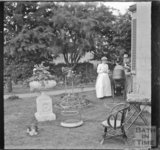 Two people and a pram in the garden of an unidentified house, c.1900s
