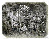 The photographer in self portrait and a group of others under a stone arch c.1890s
