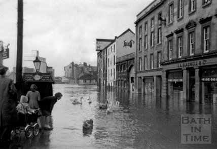 Swans swimming on Broad Quay in flood 1964
