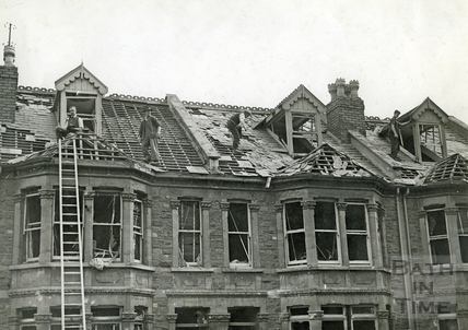 Roofers set about replacing tiles, lost from houses in Oldfield Park, Bath, May 1942
