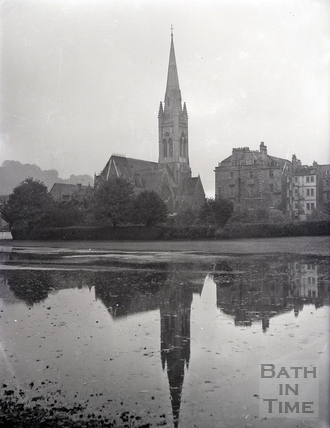 View across flooded cricket ground to St Johns Catholic Church and South Parade. Date unknown
