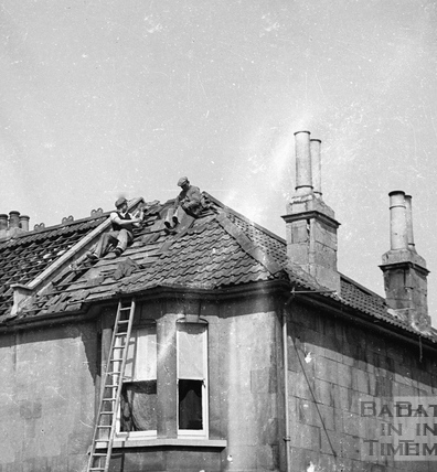 Repairing damaged roof tiles in 1942