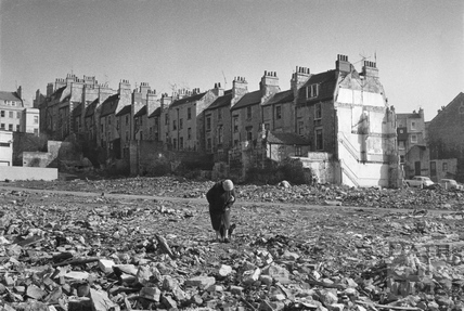 An elderly lady returns to the site of what was once her home, Lampards Buildings c.1973