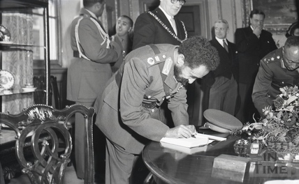 Emperor Haile Selassie signing the visitor's book in Bath during an official visit, Oct 1954