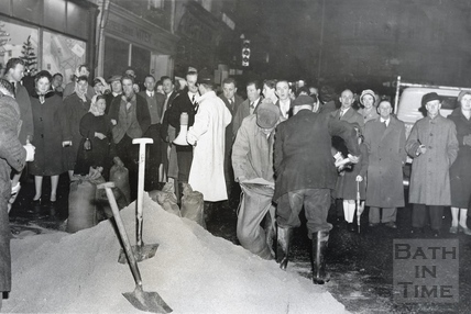 A group of people at a sand bag filling point, Southgate in floods, 1960