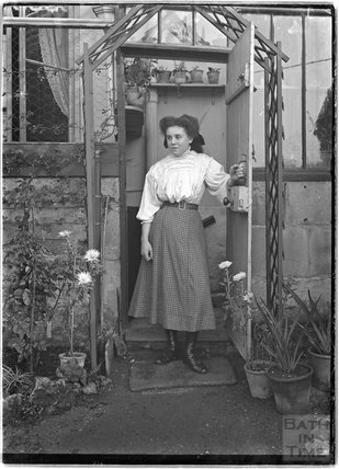 Lady in the doorway to a greenhouse c.1906