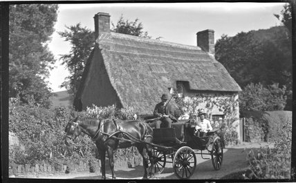 A lady in a horse drawn carriage outside a thatched cottage near Minehead 1914