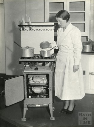 Inspecting a new stove, with a joint and pie about to be baked! c.1930s