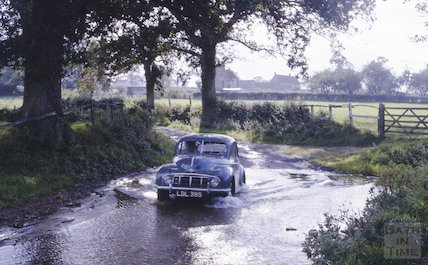 Negotiating a flooded part of the road in a Morris Minor, c.1965
