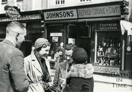 A group of shoppers chat outside Alfred Shore & Sons, Burton Street, Bath c.1935