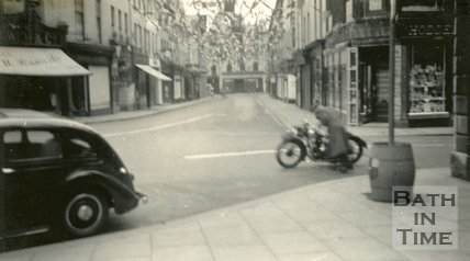 A man tending to his motorcycle, New Bond Street, Bath 1937