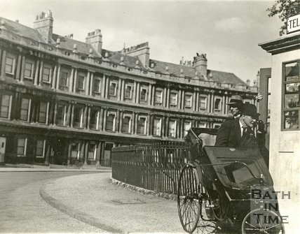 A man in a bath chair uses the public telephone that used to be at the end of Brock Street on the Circus, Bath, c.1930s