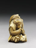 Netsuke in the form of a monkey holding a crab