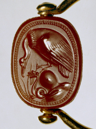 Scarab: A vulture threatens a coiled snake