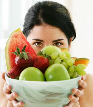 Mujer detrás de un bol de frutas