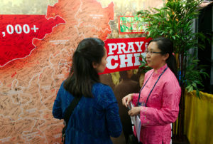 Pakka Lau (right) with a visitor to the Chinese Union Mission Booth. Exhibition at the 60th General Conference Session of the Seventh-day Adventist Church, Henry B. Gonzalez Convention Center, San Antonio, Texas, USA, July 2-11, 2015.