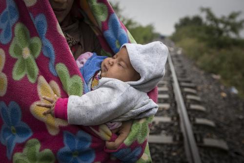 Äiti kantaa lastaan Serbiasta kohti Unkarin Rozkea. Määränpäässä pakolaiset ja siirtolaiset odottavat bussia, joka kuljettaa heidät Unkarin läpi lähellä Itävallan rajaa sijaitsevaa vastaanottokeskusta. Kuva: Jonathan Hyams/Pelastakaa Lapset