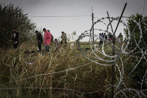 Pakolais- ja siirtolaisperheitä ratakiskoilla, jotka vievät Serbiasta Unkariin. Rautalanka-aidalla pyritään rajoittamaan ihmisten liikkumista rajan yli. Kuva: Jonathan Hyams / Pelastakaa Lapset